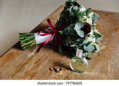 Wedding accessories. Bouquet and accessories of bride. details, Bouquet, perfume, wedding rings on a wooden table.