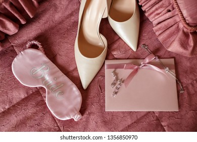 """Wedding. Accessories for bride: engagement ring and two wedding rings near bridal shoes on on high heels, perfume bottle, wedding invitation, earrings and sleep eye mask with inscription """"Bride"""""""
