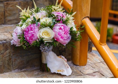 Wedding accessories. The bride's bouquet of pink peonies and white roses and a shell with wedding rings.