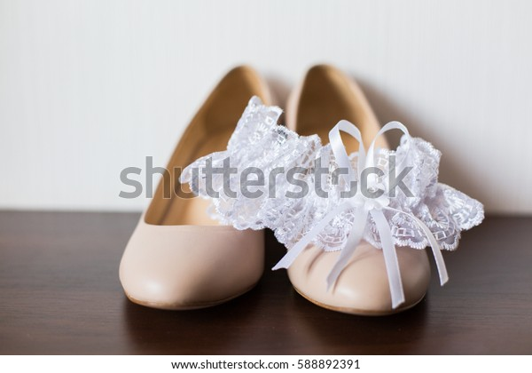 Wedding accessories: Bride's garter, shoes and delicate wedding bouquet