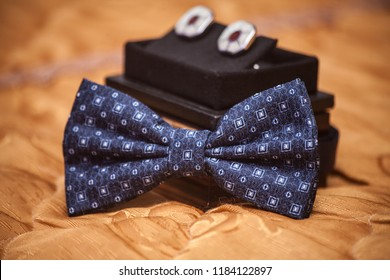 wedding accessories for the groom: a blue butterfly and cufflinks in a box on an orange cloth