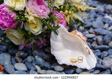 Wedding accessories. A white seashell with wedding and engagement rings lies on the sea pebbles. Wedding bouquet of the bride in the background.