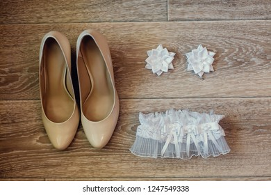 Wedding accessory of the bride. Stylish shoes, earrings, garter, standing on a light background. flat position. the view from the top. The concept of marriage.