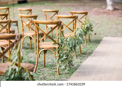 Wedding aisle with jute runner, wooden chairs and eucalyptus leaves as aisle decorations- natural, rustic wedding decor
