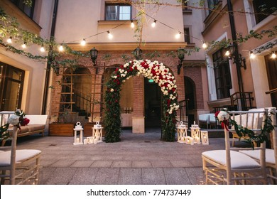 Wedding altar made of white and red roses and greenery stands on the backyard