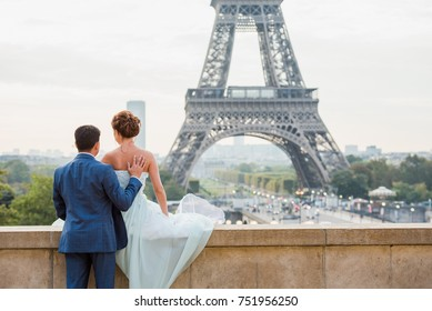 Wedding anniversary celebration in Paris. Beautiful wedding dresses and hair style of the woman who is sitting and looking at the Eiffel Tower and a man, holding her.