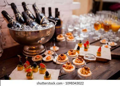 Wedding appetizer. Fruit dessert sandwiches served on the table, catering, champagne bottle in ice bucket