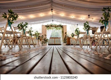 Wedding arch for wedding ceremony. Beautiful wedding decor in rustic style and chairs for guests