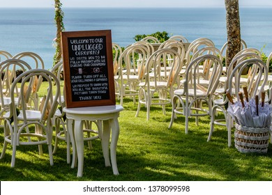 Wedding arch for a ceremony decorated with fresh flowers, chairs and sun umbrellas for guests among palm trees near the ocean. Blackboard sign saying to turn cell phones off for unplugged ceremony.