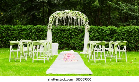 wedding arch and chairs on the green grass in the park.Wedding ceremony decoration