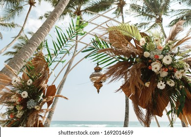 Wedding arch decorated with flowers for beach ceremony against the sea landscape. Tropical wedding ceremony in boho/ rustic style