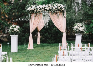Wedding arch decorated with flowers, white chairs and flowers bouquet