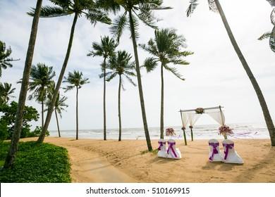 wedding arch decorated on tropical sand beach, outdoor beach wedding setup.