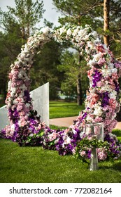 Wedding arch of flowers with torches at an outdoor ceremony.