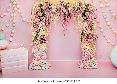 Wedding arch indoors. Festive decorations with flowers and colorful balloons on pink background.