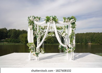 wedding arch on the shore, decoration with white flowers