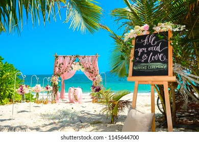 Wedding arch on the shore of a tropical island under green fingers. Offsite marriage registration on a tropical beach.