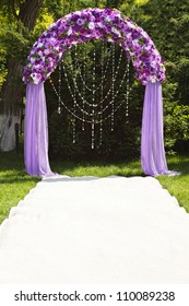 Wedding arch of purple roses.