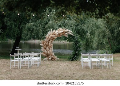 Wedding arch under the tree and chairs for guests. Outside ceremony place. Wedding arch. Wedding ceremony place