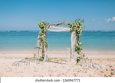 Wedding arch with white flowers at blue ocean in tropical island. Wedding ceremony.