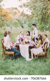 The wedding arranged in the sunny forest. The best man is saying the sentiment dedicated to happy newlyweds and the guests at the table are listening to.
