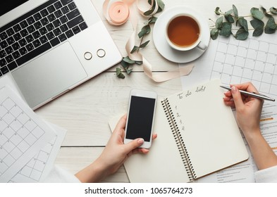 Wedding arrangement background. Female hands preparing for marriage, using laptop, smartphone, paper calendars and planners, top view. Bridal wallpaper with copy space on to do list