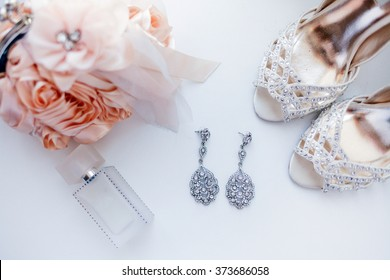 wedding attributes such as earrings, shoes, perfume, handbag
