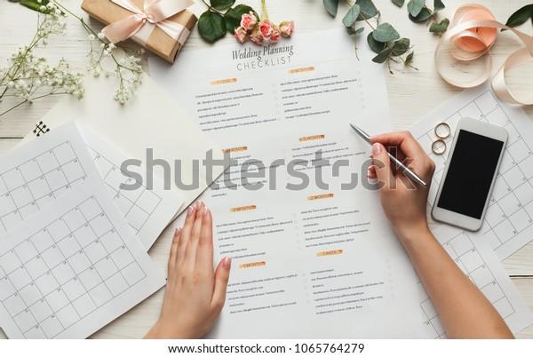 Hochzeitshintergrund mit Checkliste und Kalender. Weibliche Hände, die die Ehe arrangieren, Planer auf weißem Holztisch mit viel zärtlichem Brautzeug füllen, Draufsicht