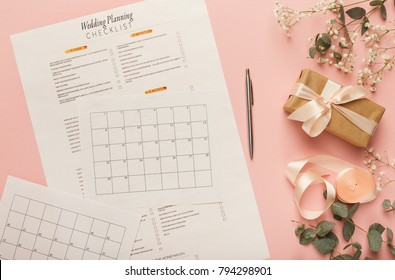 Wedding background with checklist and calendar. Paper planners on pink table with lots of tender bridal stuff, top view