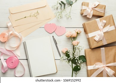 Wedding background with checklist. Paper planner and craft envelopes on white wooden table with lots of tender bridal stuff, top view