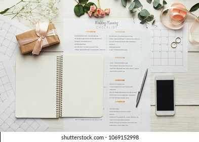 Wedding background with checklist. Paper planner and wedding rings on white wooden table with lots of tender bridal stuff, top view