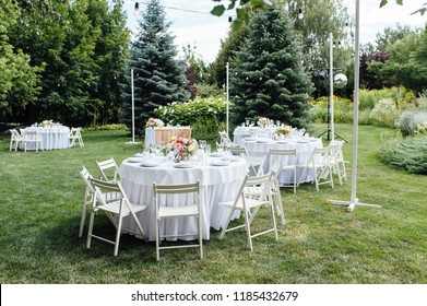 Wedding. Banquet. Chairs and honeymooners table decorated with candles,