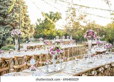 Wedding. Banquet. Chairs and honeymooners table decorated with candles, served with cutlery and crockery and covered with a tablecloth. The table stands on a green lawn in the backyard banquet area.