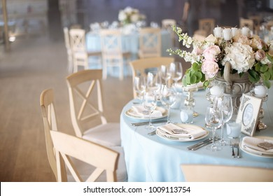 Wedding. Banquet. The chairs and round table for guests, served with cutlery, flowers and crockery and covered with a tablecloth