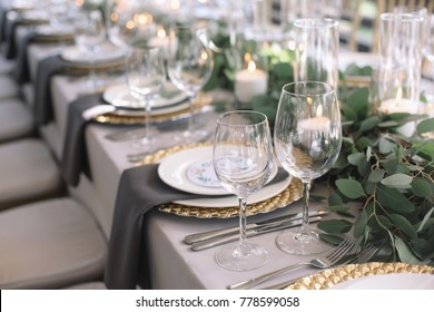 Wedding. Banquet. The chairs and round table for guests, served with cutlery, greenery flowers and crockery and covered with a white tablecloth