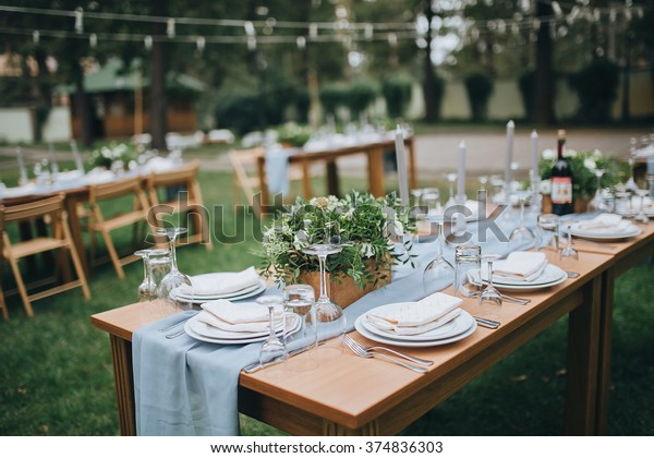 Wedding. Banquet. The chairs and table for guests, decorated with candles, served with cutlery and crockery and covered with a tablecloth. The table stands on a green lawn in the backyard banquet area
