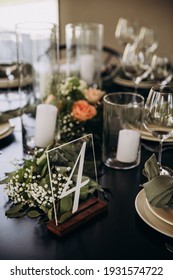 Wedding banquet. The festive table is served with plates with napkins and name cards, glasses and cutlery, and decorated with flower arrangements and candles