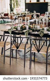 Wedding banquet. Festive tables in the bright room are served and decorated with flower arrangements and candles, there are chairs next to the tables, a carpet is on the floor
