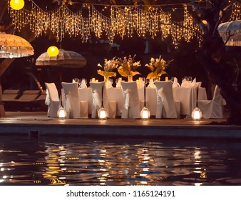 Wedding Banquet or gala dinner decorated with garlands. Festive table set up decor for wedding, party or event