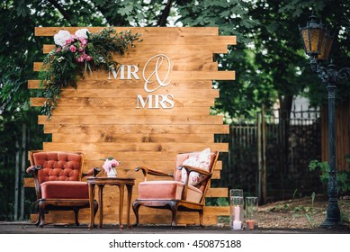 Wedding. Banquet. Mr. & Mrs. signs on wooden board decorated by flowers and greenery and lounge zone including chairs and tables.