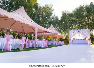 Wedding banquet outdoor in marquees on lawn decorated pink silk, lace and flowers