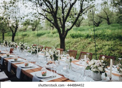 Wedding banquet table in a garden decorated with a composition of white flowers and greenery, there are cutlery and candles