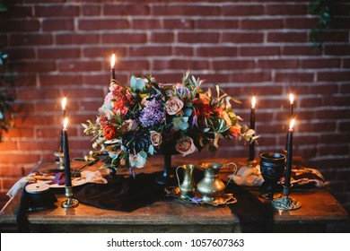 Wedding. Banquet. Table, served with cutlery, flowers, candles and crockery on the red brick wall. Black candles. Red, violet and black flowers.