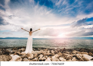 Wedding at the beach. Island wedding. Beautiful bride standing with open arms.  Relaxed woman enjoying sun, freedom and life an beautiful beach in sunset. Young lady feeling free, relaxed and happy.
