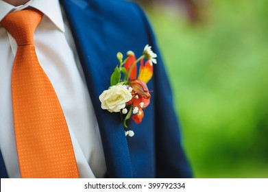 wedding beautiful boutonniere on suit of groom. Man in blue suit, shirt and orange tie.