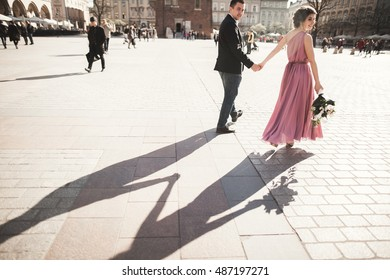 wedding. beautiful couple, bride with pink dress walking in the old city Krakow, their shadows