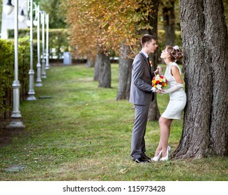 Wedding - beautiful young bride and groom standing in a park outdoors holding hands and show each other tongues