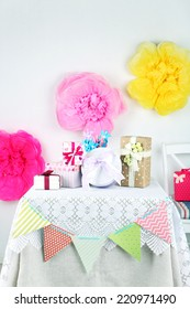 Wedding or birthday gifts on decorated table, on bright background