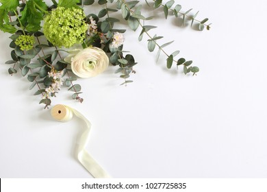 Wedding or birthday mock-up scene with floral bouquet of Persian buttercup, Ranunculus flower, eucalyptus leaves, pink cherry tree blossoms and spool of silk ribbon Feminine styled stock image. Flat l