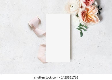 Wedding, birthday stationery mock-up scene. Blank menu card. Decorative floral corner and ribbon. Green leaves, pink English roses and ranunculus flowers. Concrete table background. Flat lay, top view